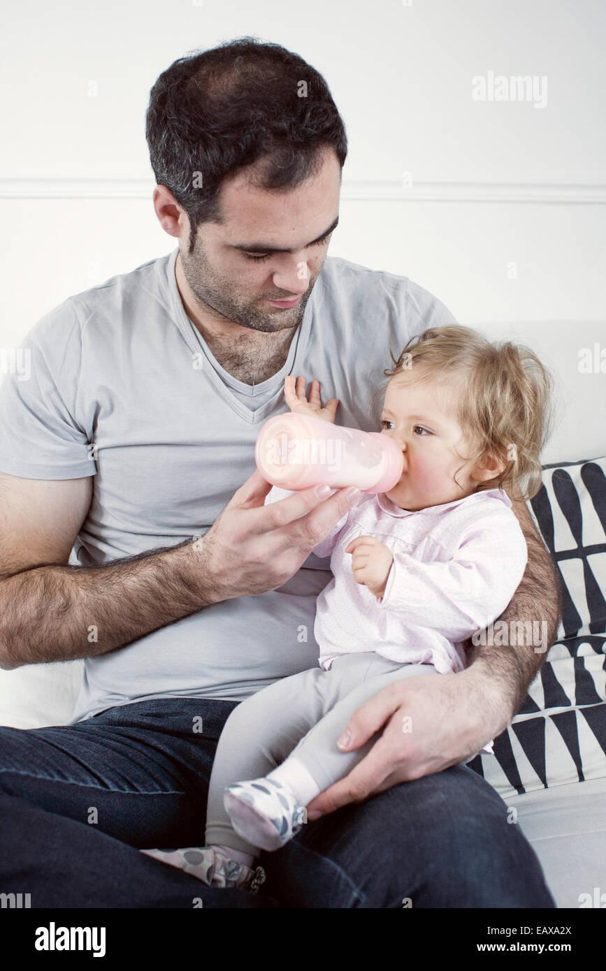 Vater hält Babymädchen auf Schoß, ihr mit der Flasche füttern Stockbild