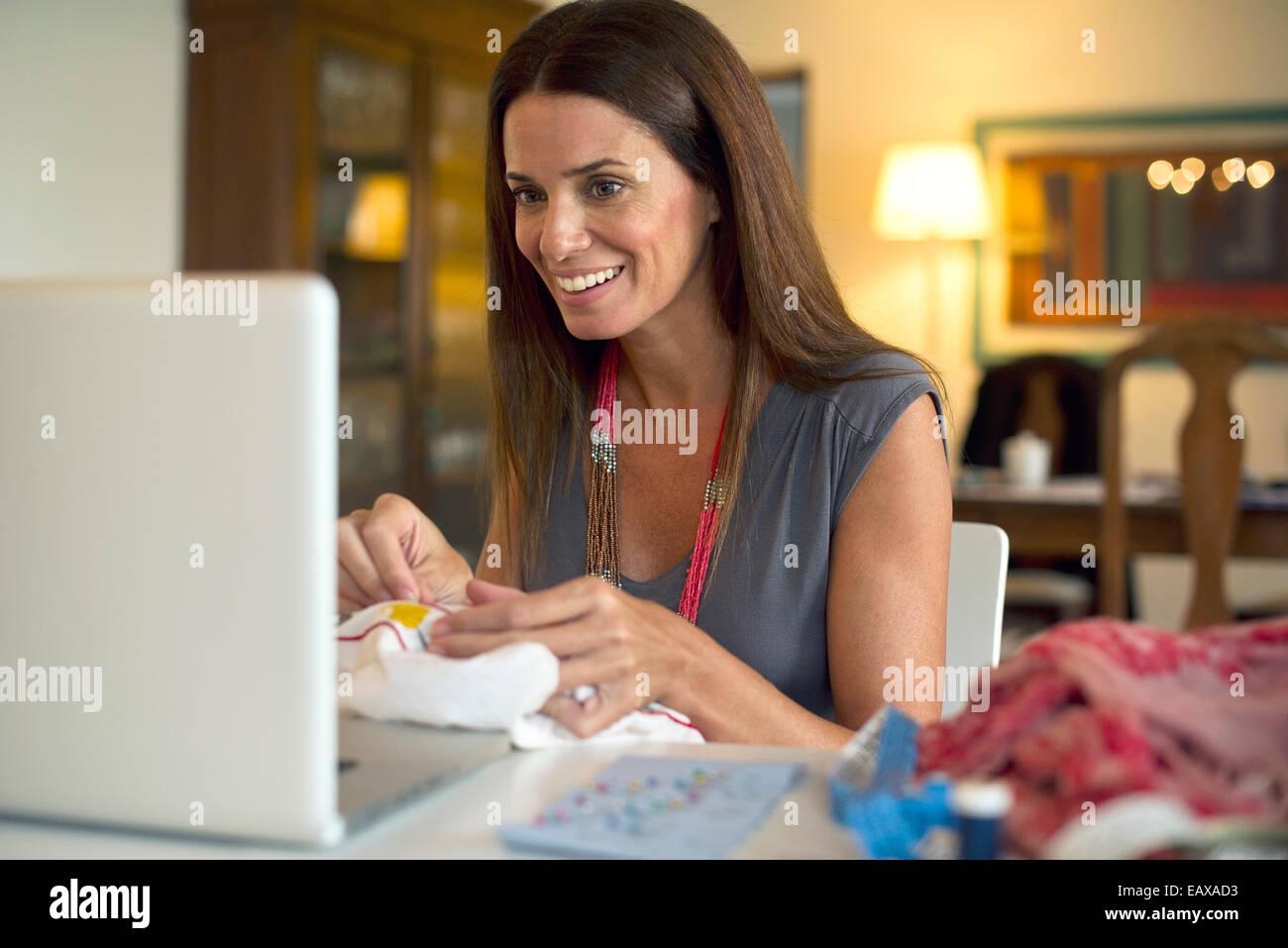 Frau auf der Suche auf Laptop-Computer während des Nähens Stockbild
