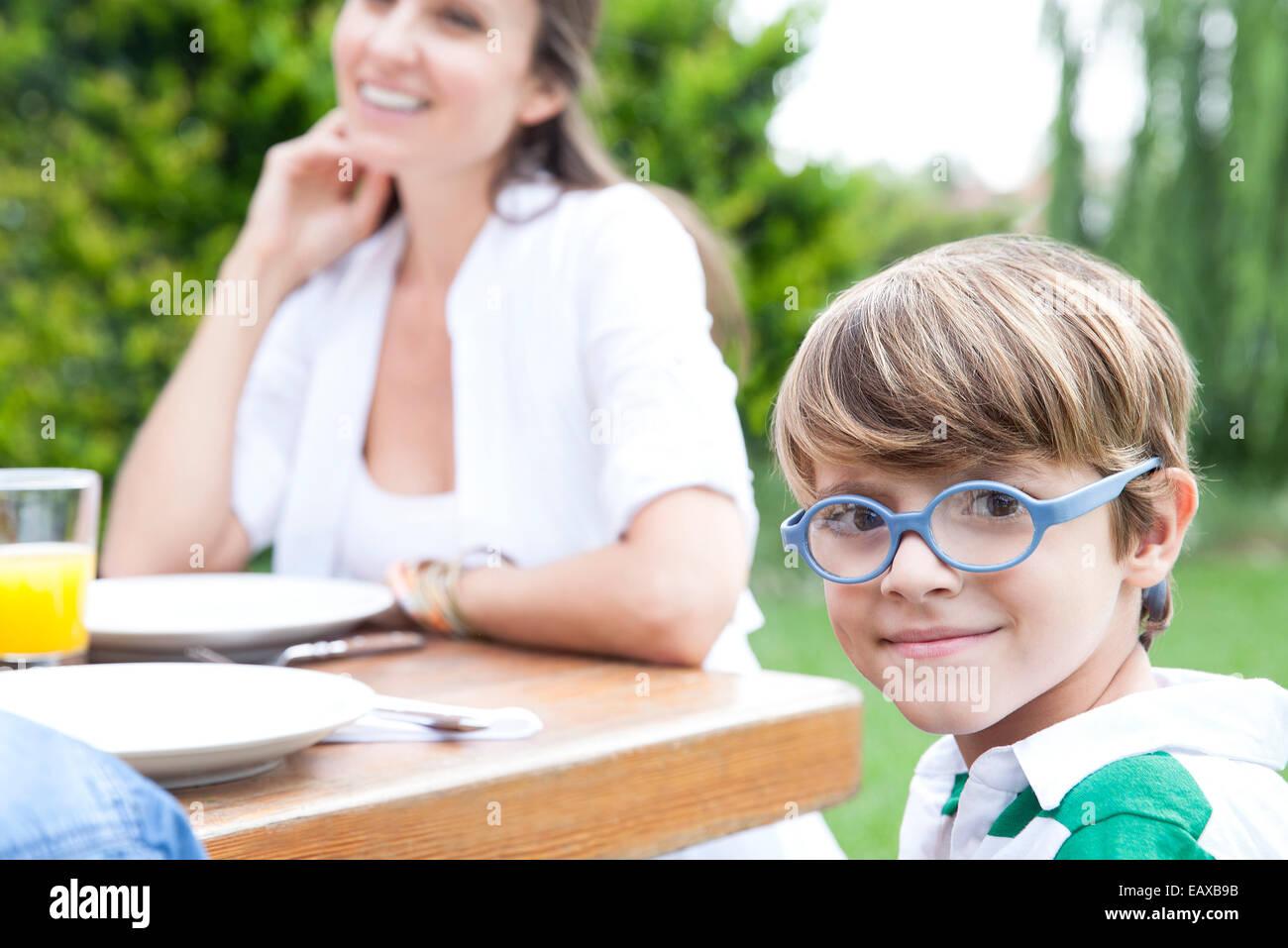 Kleiner Junge sitzt am Tisch im Freien mit Familie, lächelnd in die Kamera Stockbild
