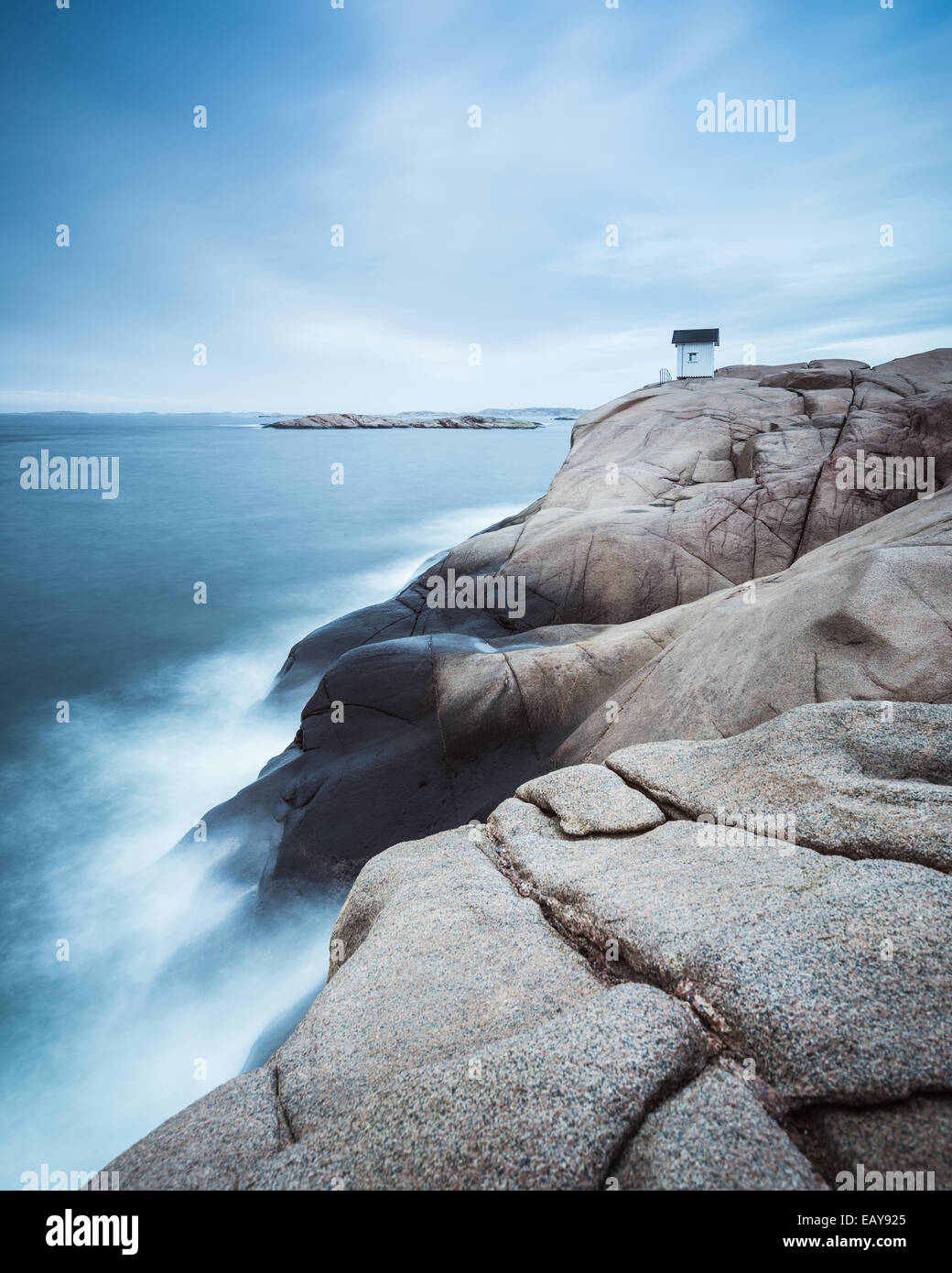 Kabine auf Klippe in der Nähe von Meer mit dramatischer Himmel Stockbild