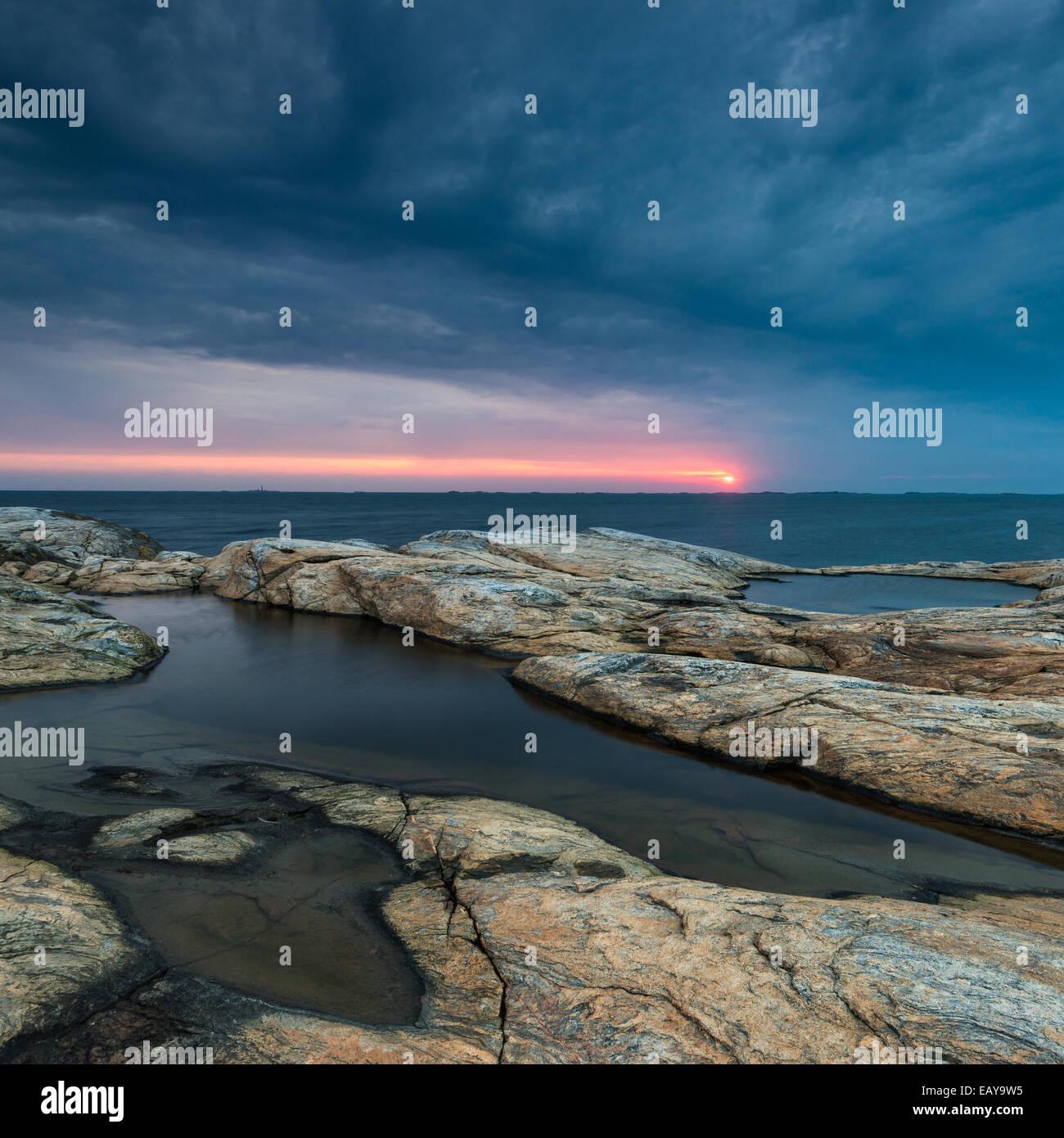 Felsige Küste mit dramatischer Himmel bei Sonnenuntergang Stockbild