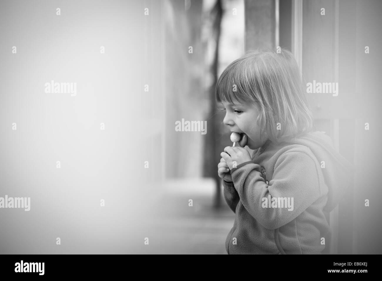 ein Liitle Mädchen heimlich Essen einen leckeren Lutscher Stockbild