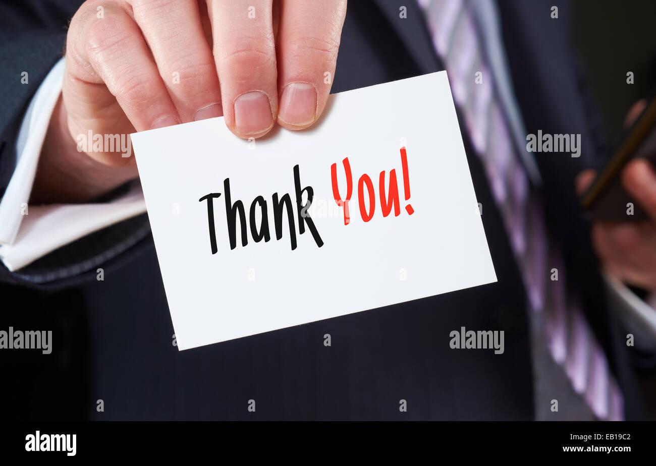Ein Geschäftsmann hält eine Visitenkarte mit den Worten: Vielen Dank, darauf geschrieben. Stockbild