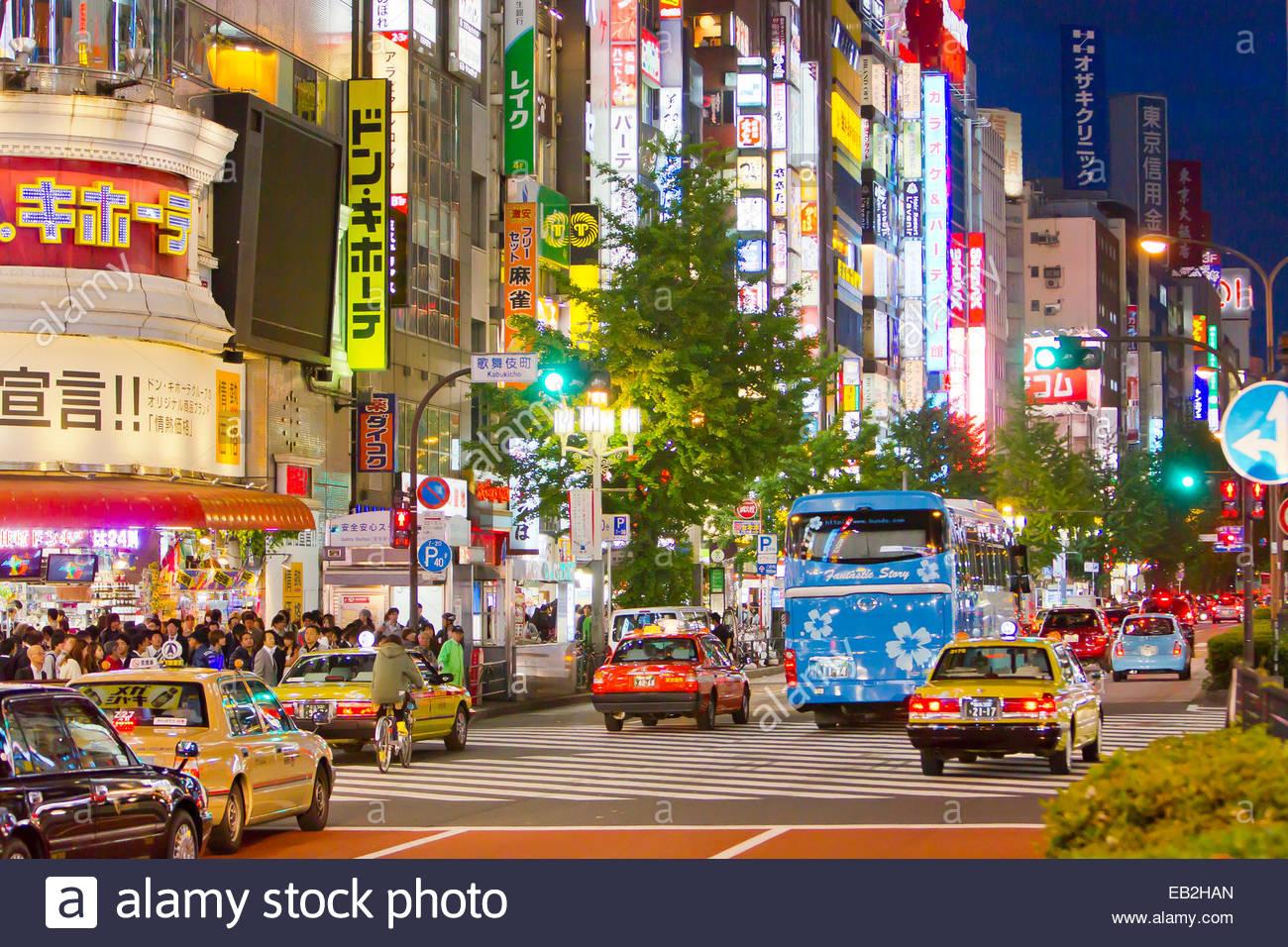 Bunte Zeichen und Verkehr im Stadtteil Shinjuku nachts. Stockbild