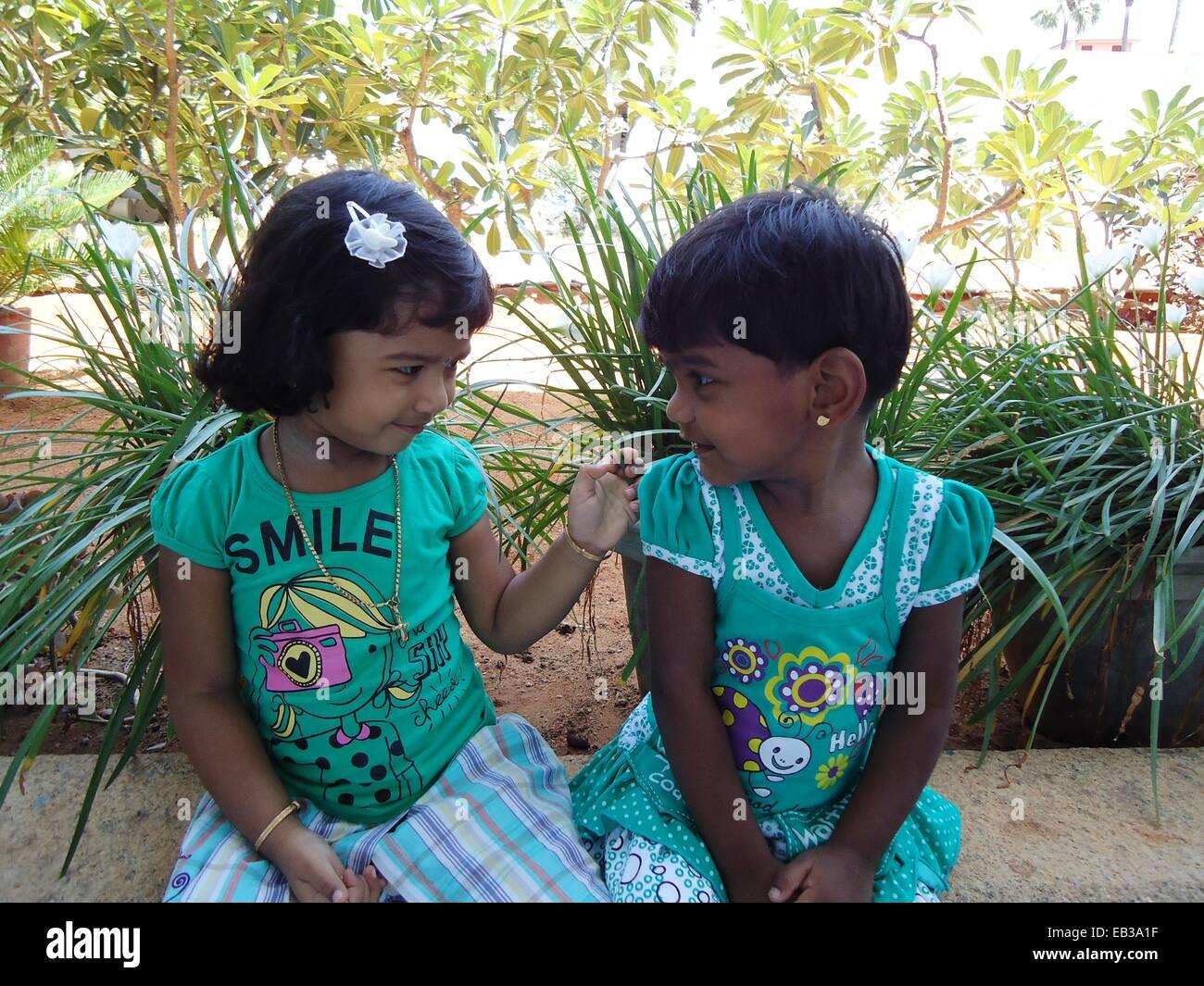 Indien, Tamil Nadu, Thoothukudi, Kalugumalai, zwei Mädchen (2-3) auf Brüstung Blumenbeet im Garten sitzend, Stockbild