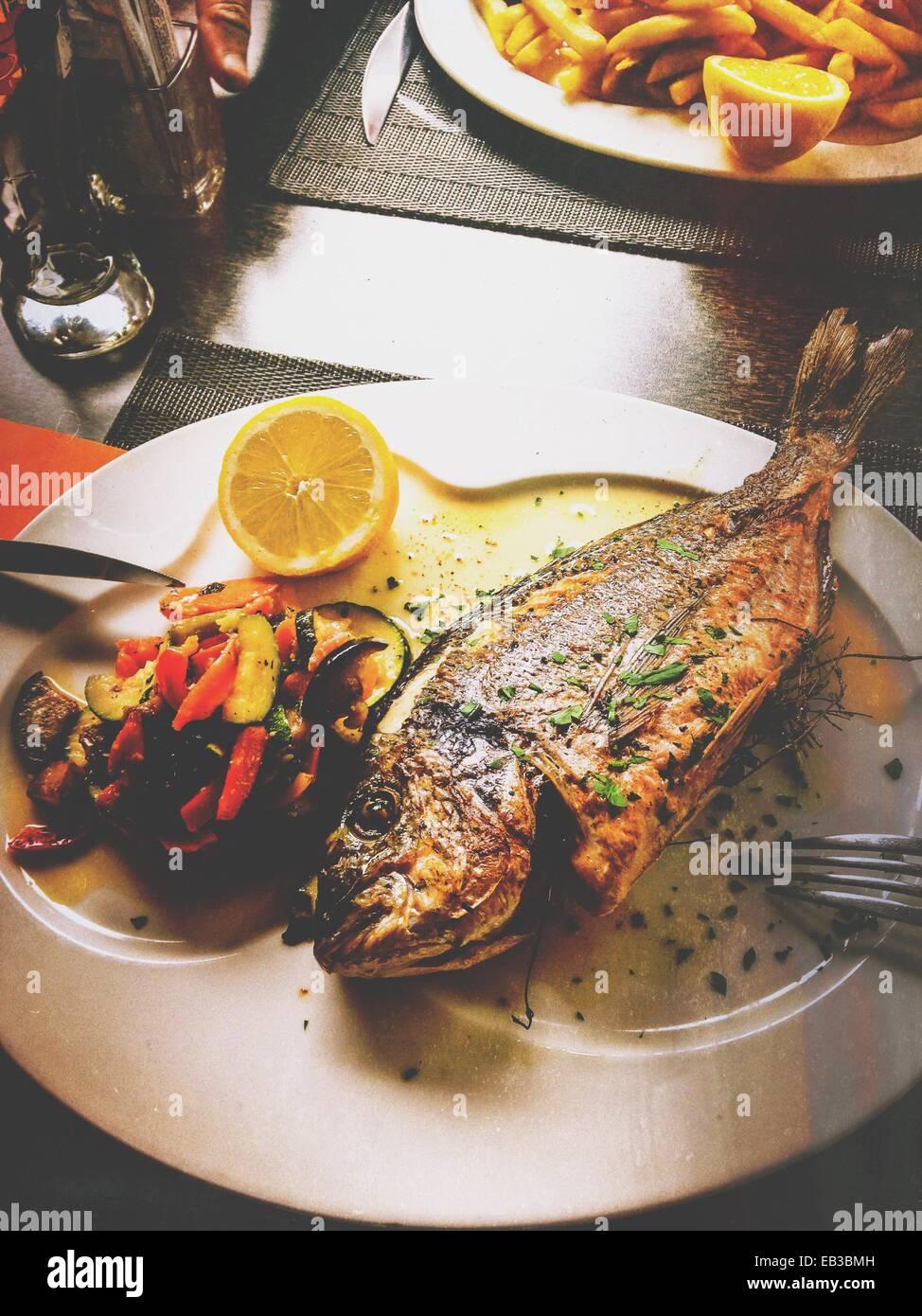 Gegrillter Fisch mit gebratenem Gemüse Stockbild
