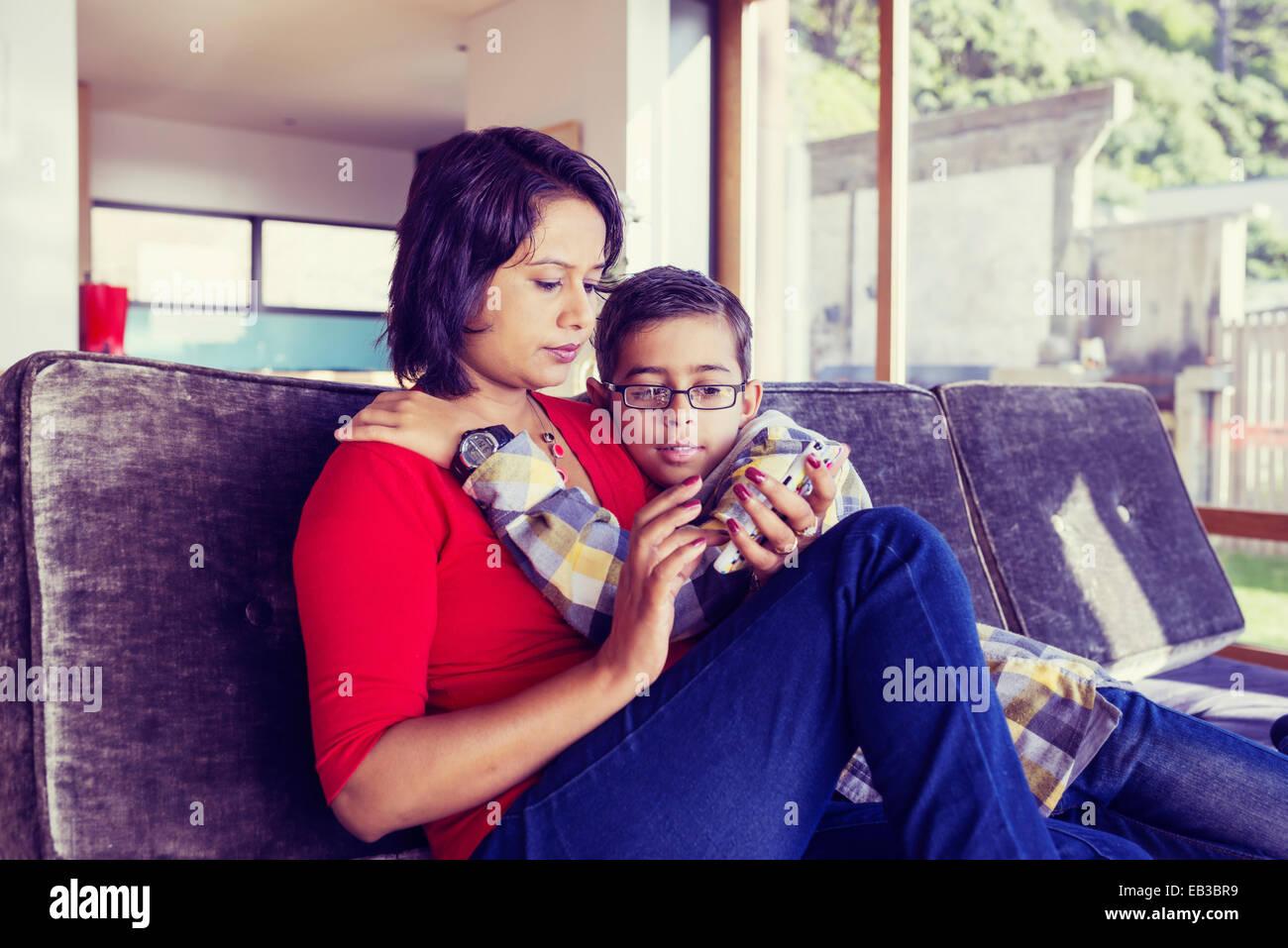 Mutter und Sohn mit Handy im Wohnzimmer Stockfoto