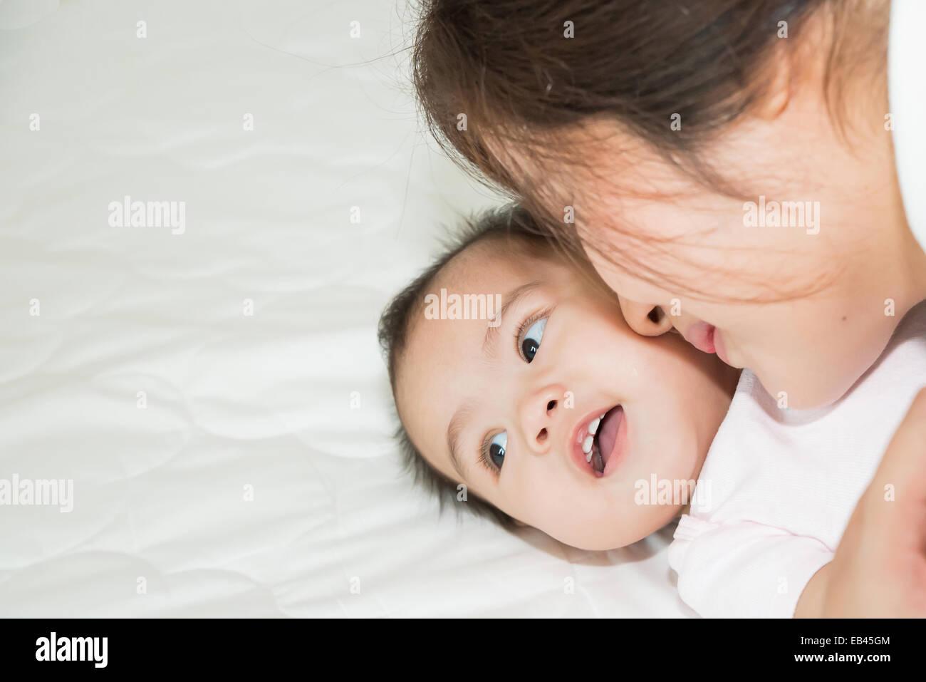 Glückliche Familie fröhlich. Asiatische Mutter und Baby küssen, lachen und umarmen Stockbild