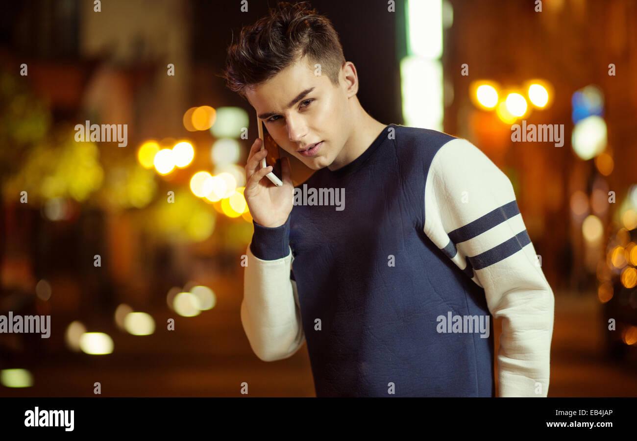 Teenager charmante Kerl reden auf dem smartphone Stockbild
