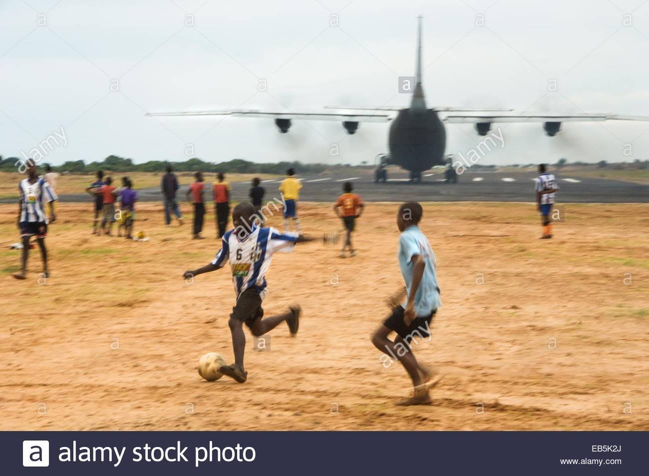 Jungen spielen Fußball neben der Landebahn bei Cuito Cuanavale. Der Ort spielte eine Schlüsselrolle in Stockbild