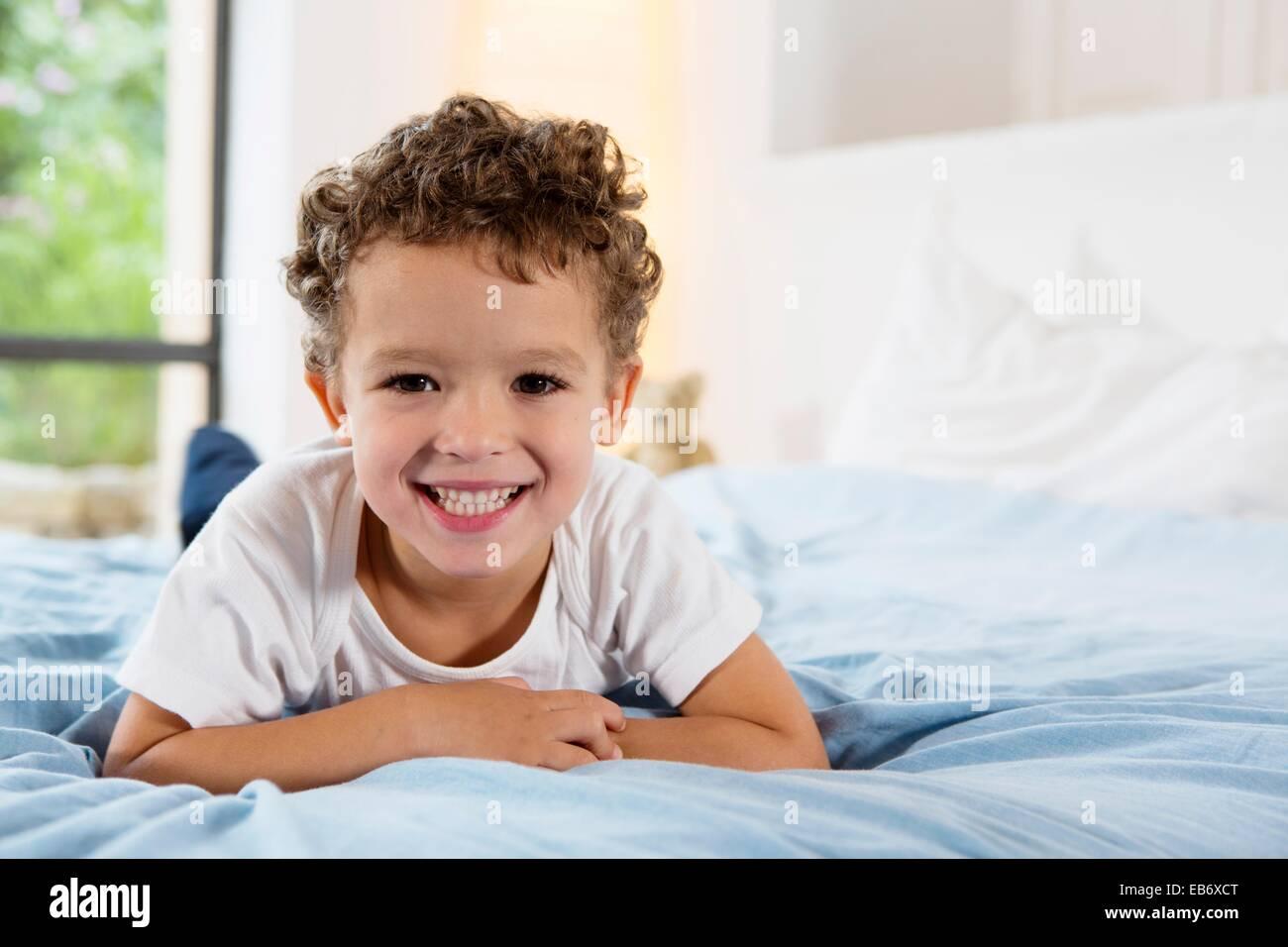 vier jahre alter junge auf einem bett liegend stockfoto bild 75755144 alamy. Black Bedroom Furniture Sets. Home Design Ideas