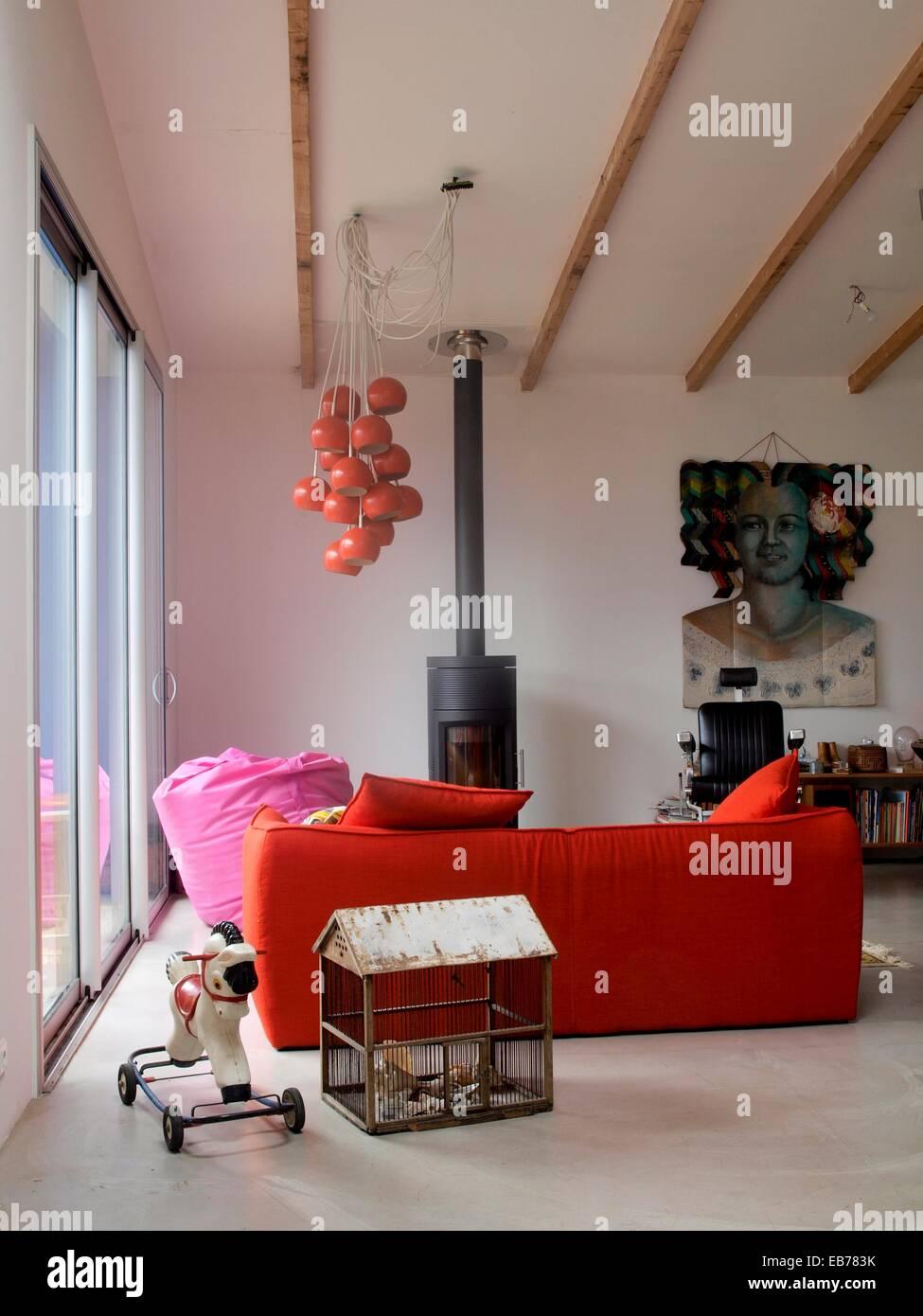 Lounge. Spielzeugpferd auf Rädern. Käfig-förmige Haus. Rotes Sofa ...