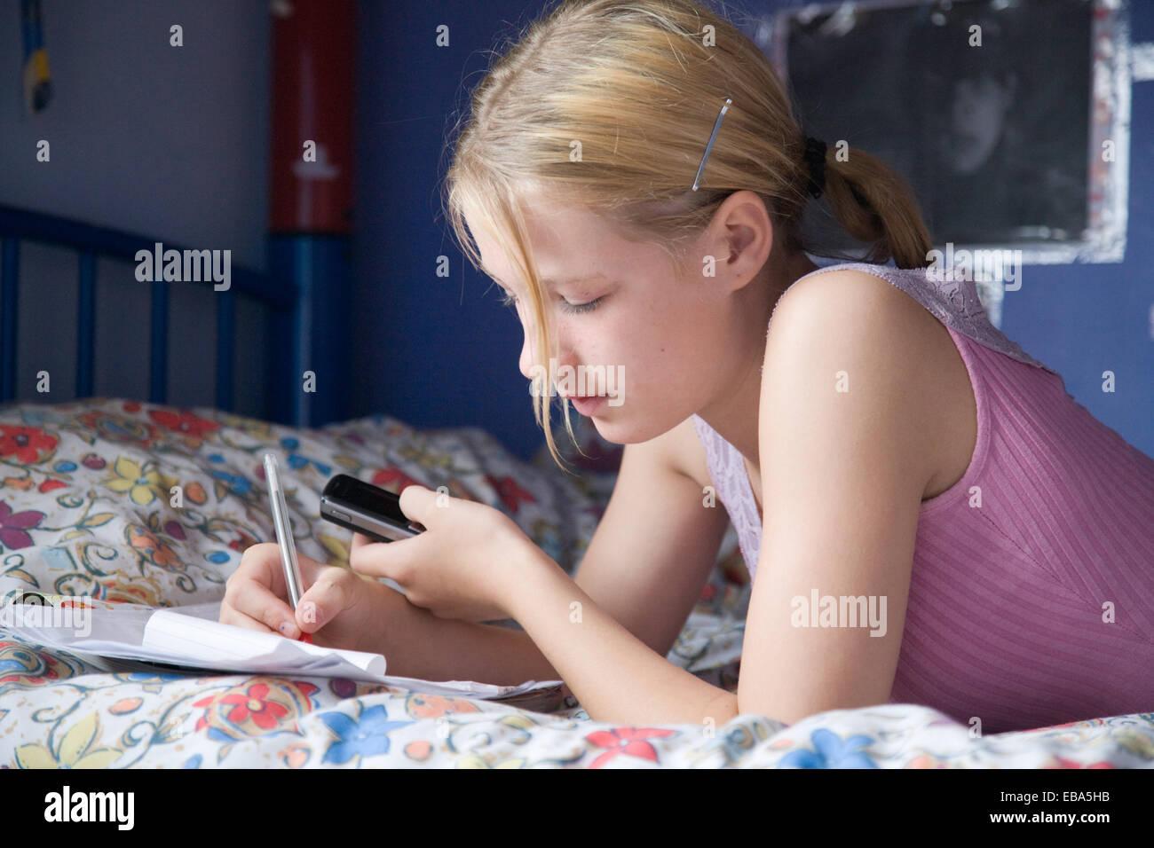 Teenager-Mädchen auf ihrem Bett liegend mit Handy und