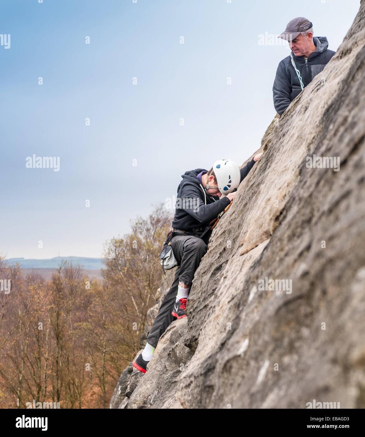 Young rock Kletterer am birchenfarbig Rand im Peak District Derbyshire - mit einem Instruktor führt ein Teenager Stockbild