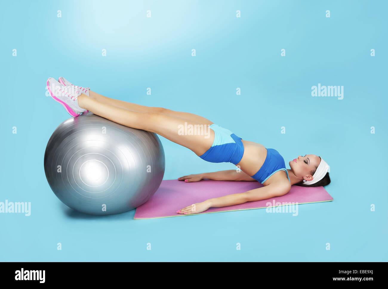 Bauch-Übung. Sportliche Frau mit Fitness-Ball Stockbild