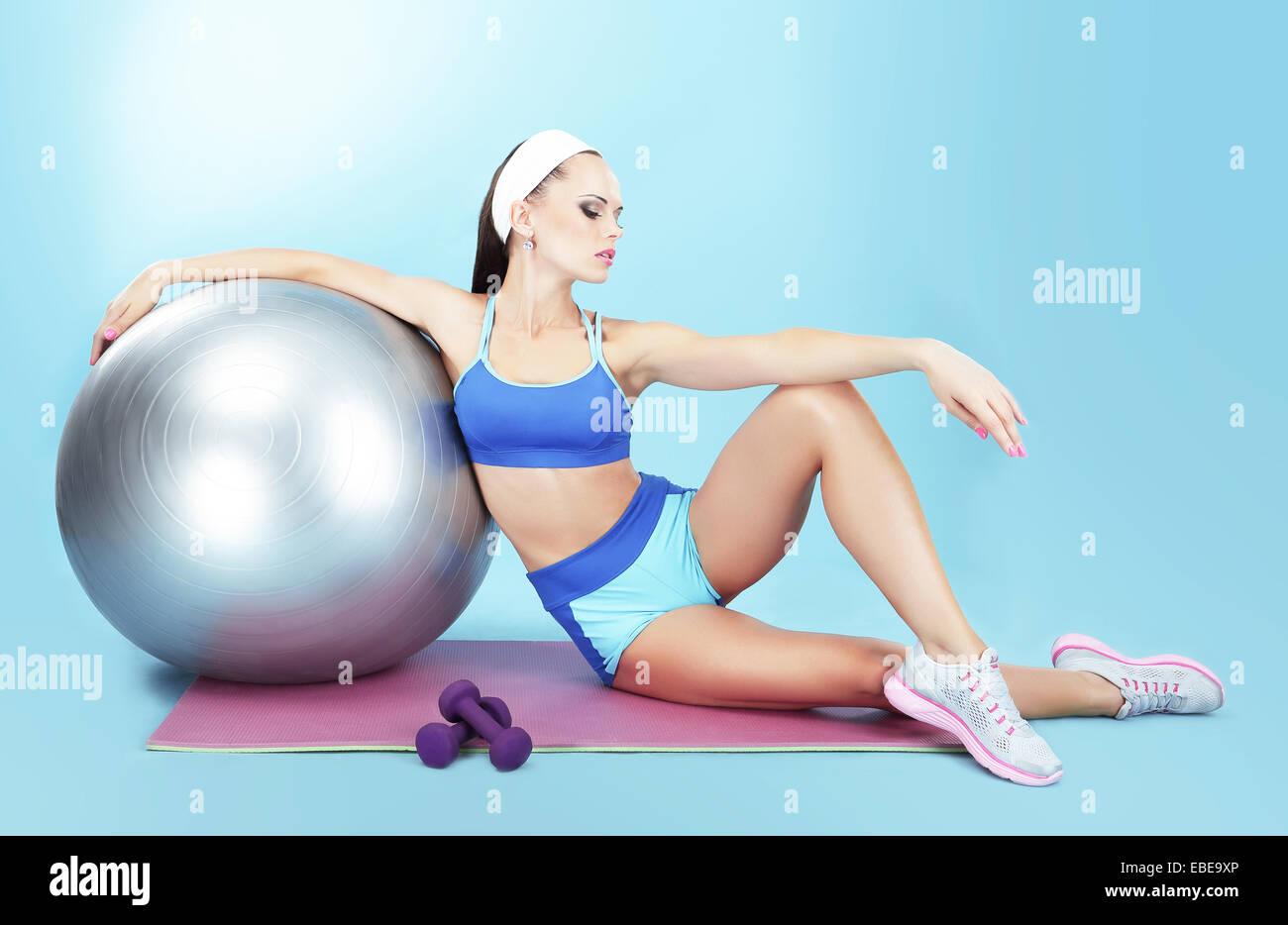 Ruhe. Sportlerin mit Sportgeräten - eine Fitness-Ball und Hanteln Stockbild