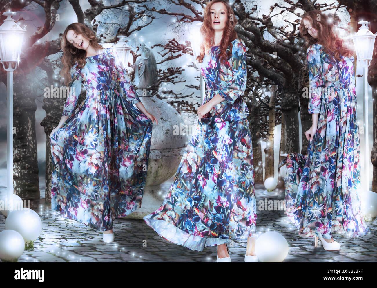 Inspiration. Fantasie. Frauen in geblümten Kleidern unter Bäumen Stockbild