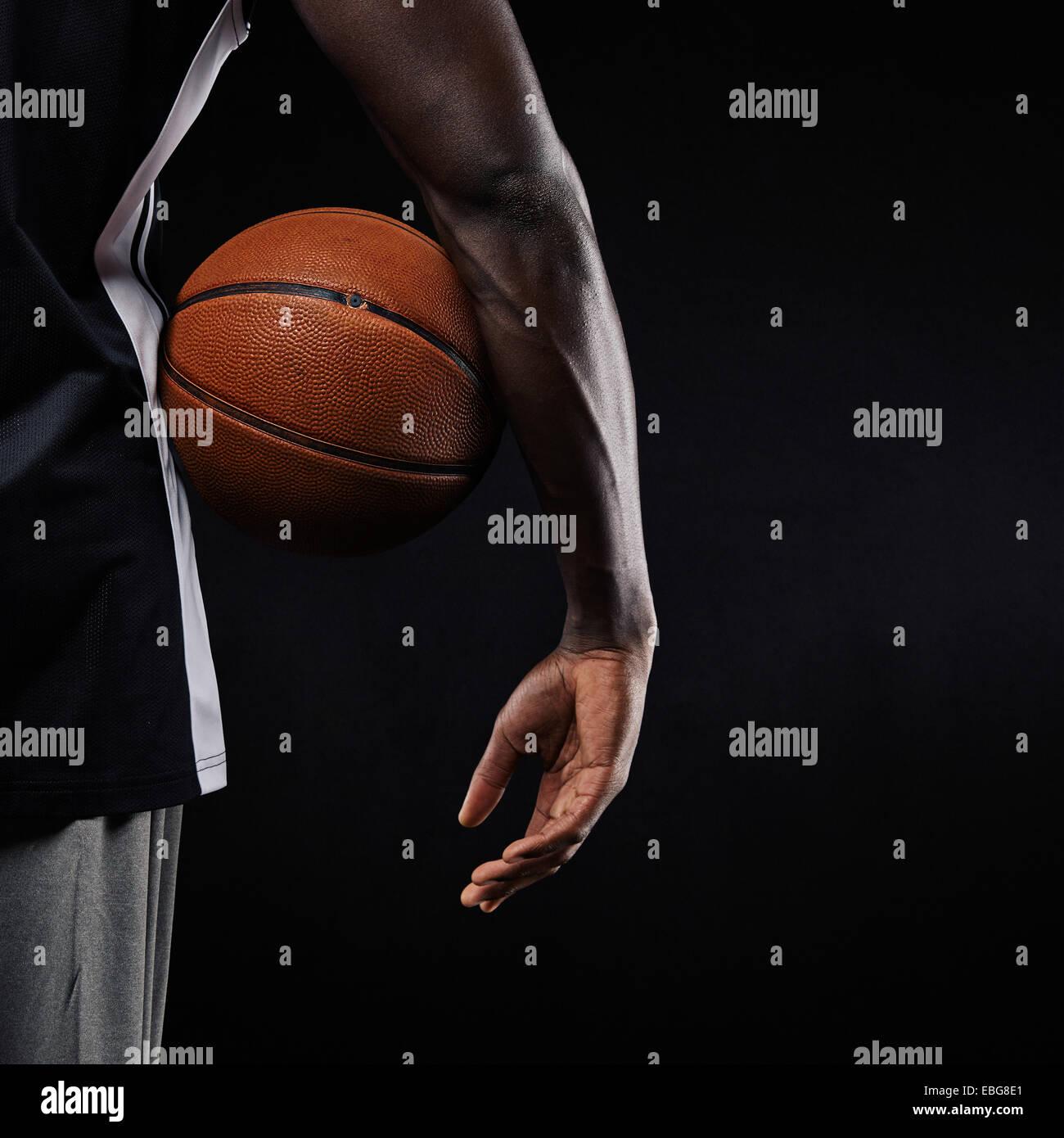 Nahaufnahme eines Basketballs in der Hand eines jungen afrikanischen Athleten vor schwarzem Hintergrund mit Textfreiraum. Stockfoto