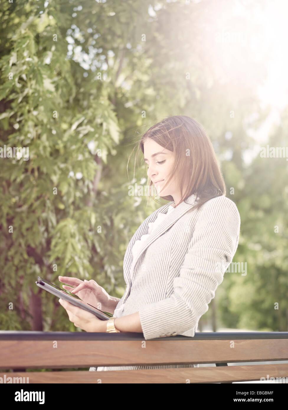 Frau trägt ein Geschäft passen stehend mit einem Tabletcomputer hinter einer Parkbank, Innsbruck, Tirol, Stockbild
