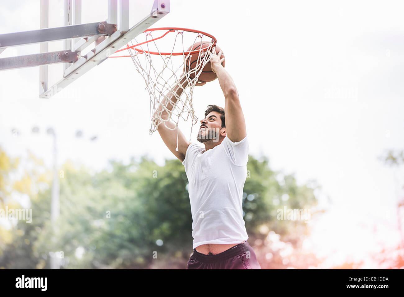 Junge männliche Basketball-Spieler mit Ball springen zu Punkten Stockbild