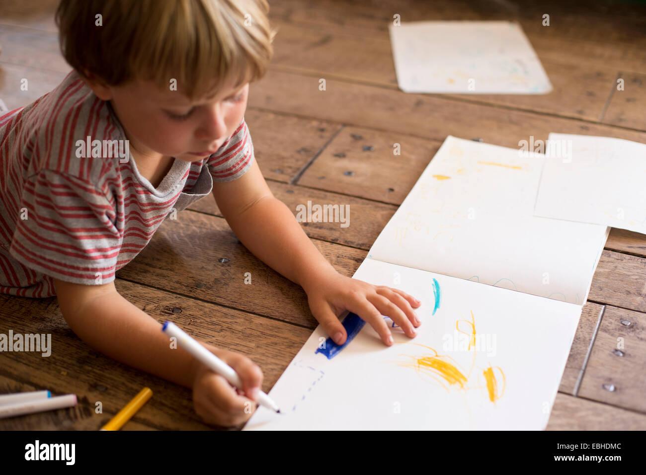 Junge, Zeichnung auf Papier Stockbild