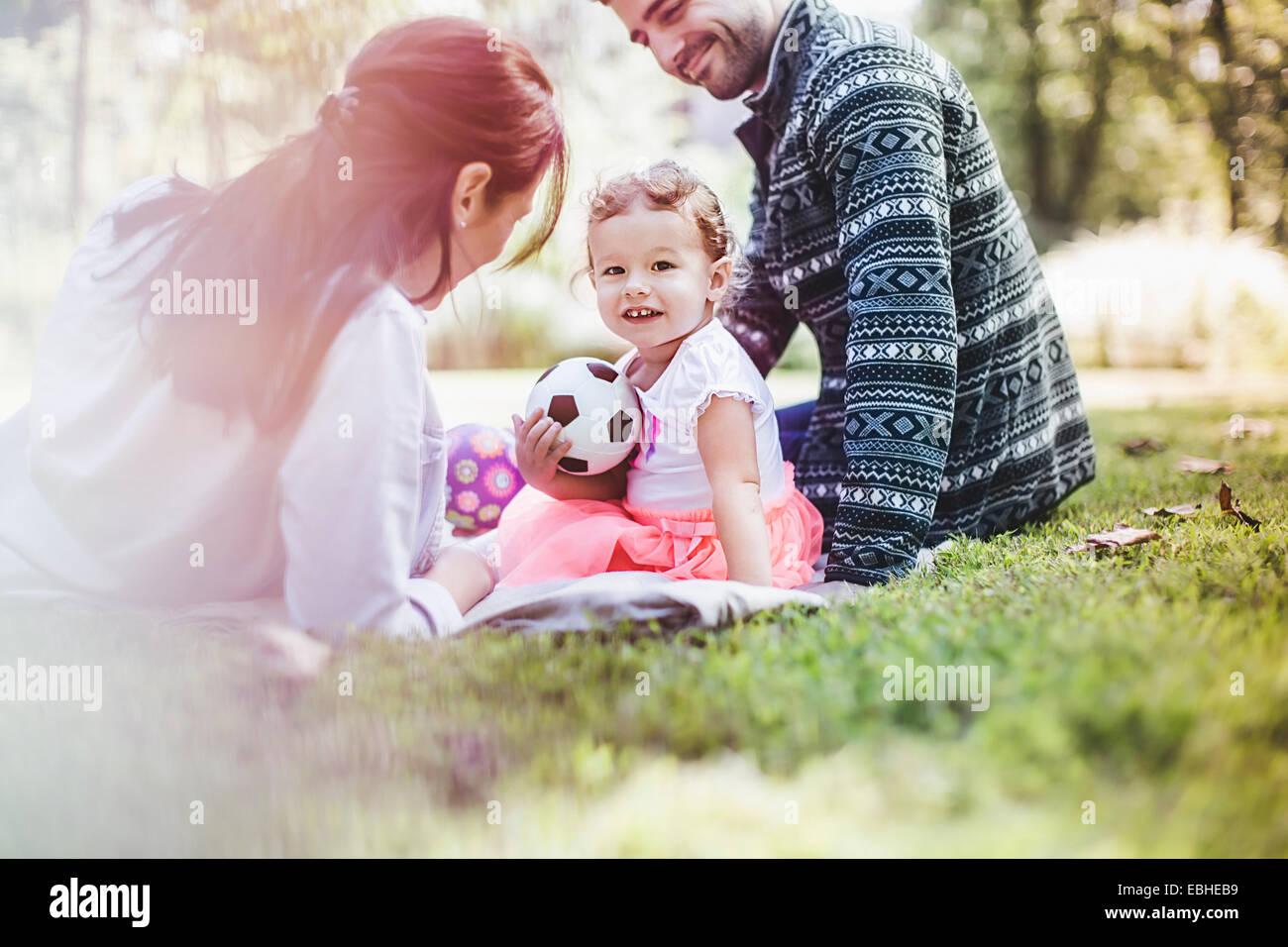 Eltern und Tochter spielen im Garten Stockbild