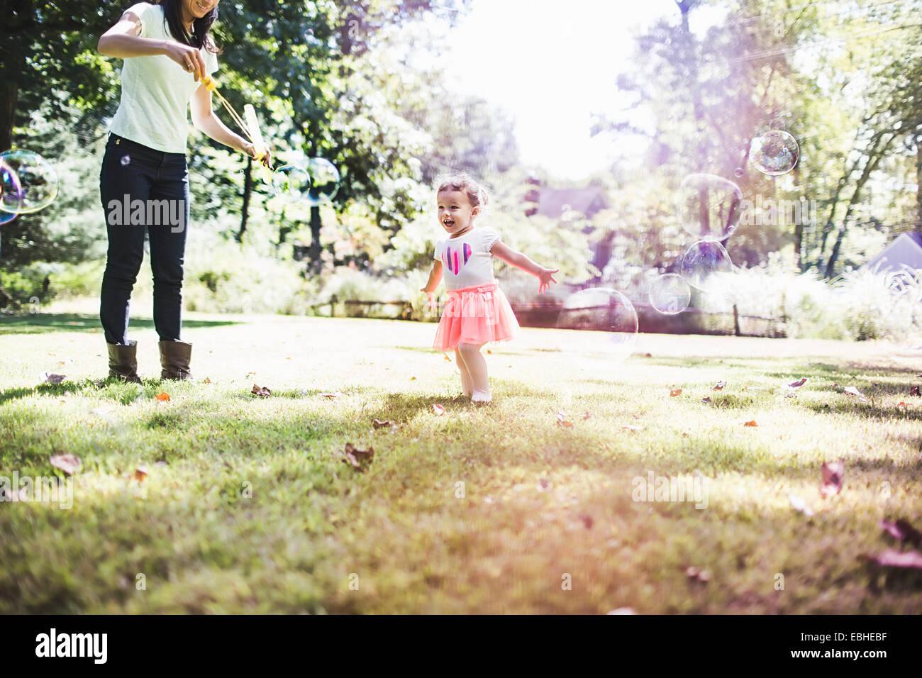 Mutter und Tochter spielen Luftblasen im Garten Stockbild