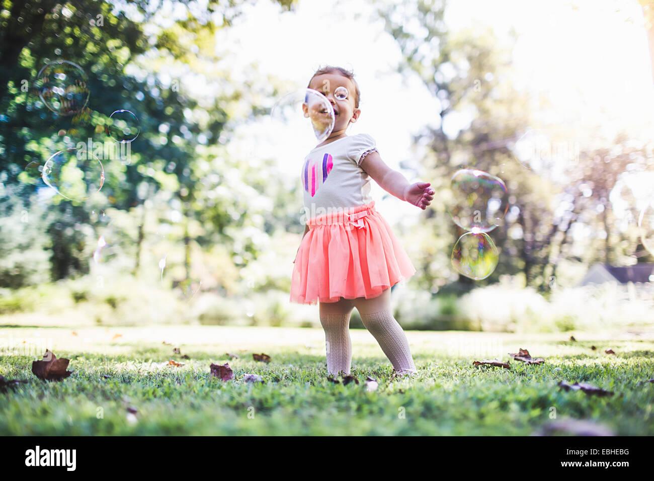 Babymädchen spielen mit Luftblasen im Garten Stockbild