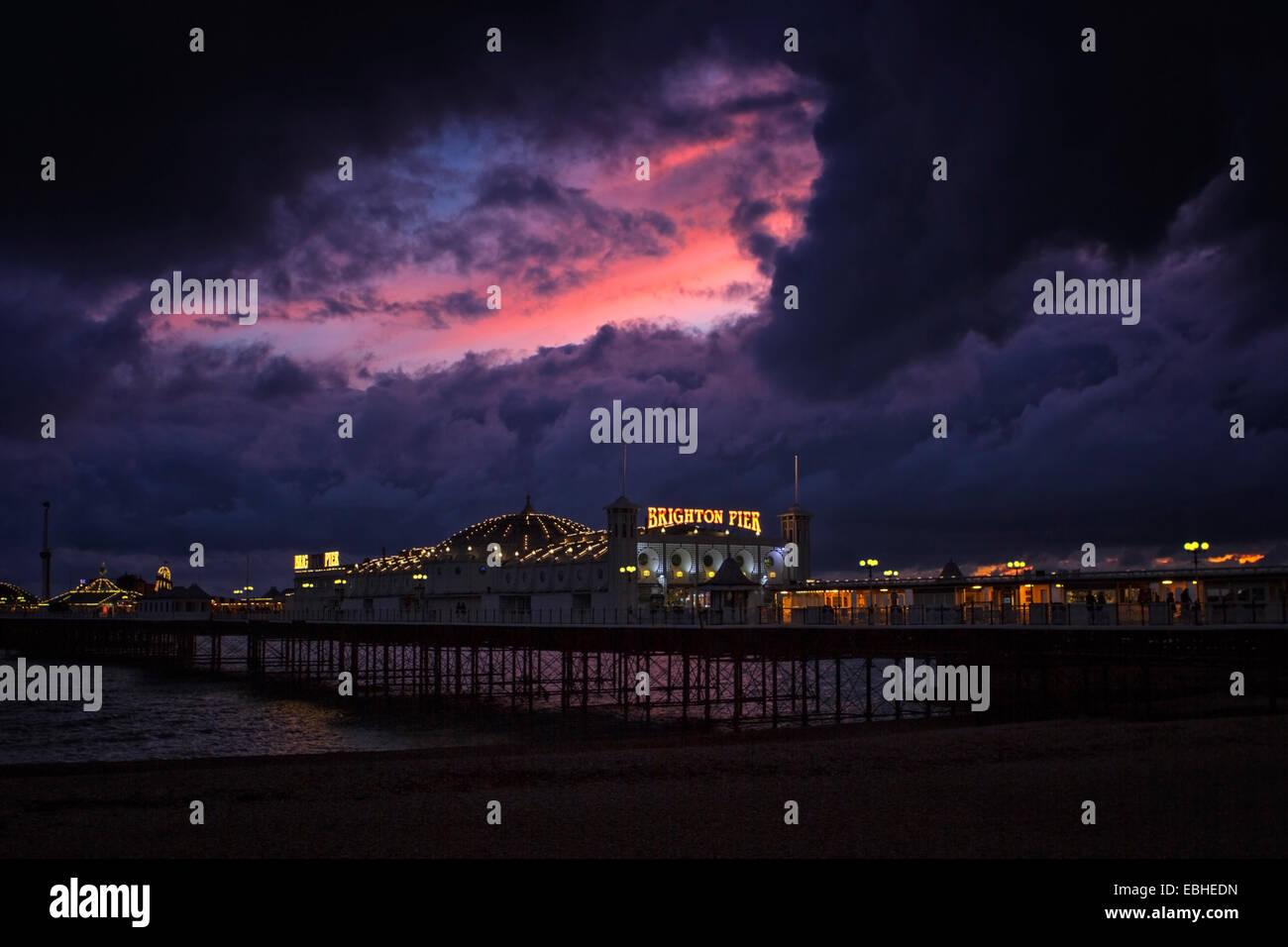 Gewitterwolken und Sonnenuntergang über Brighton Pier Stockbild
