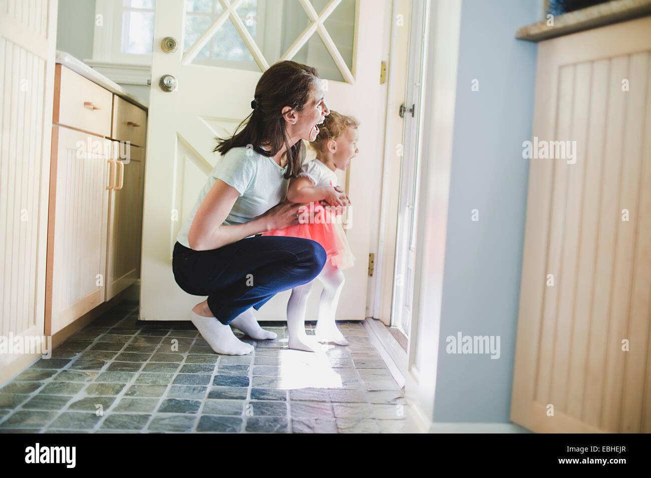 Mutter und Tochter lachend an Tür Stockbild