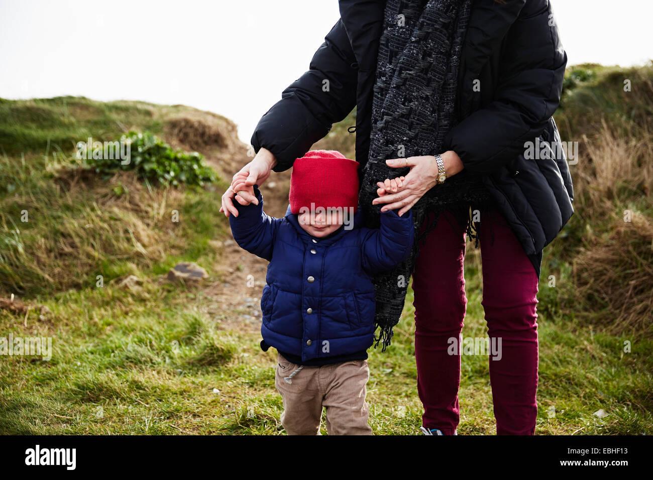 Männliche Kind und Mutter Hand in Hand gehen in Düne Stockbild