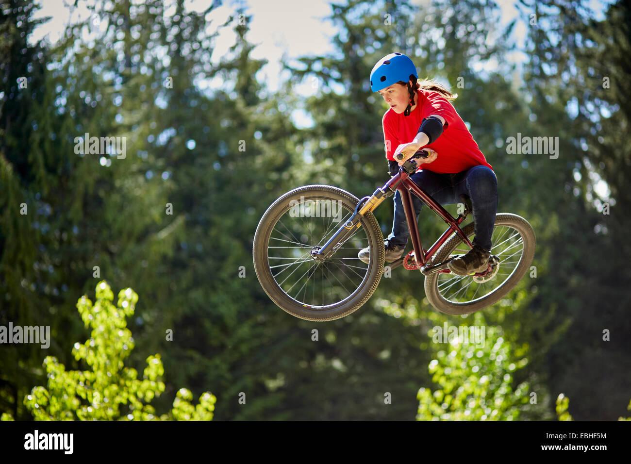 Junge weibliche bmx-Biker springen Luft im Wald Stockbild