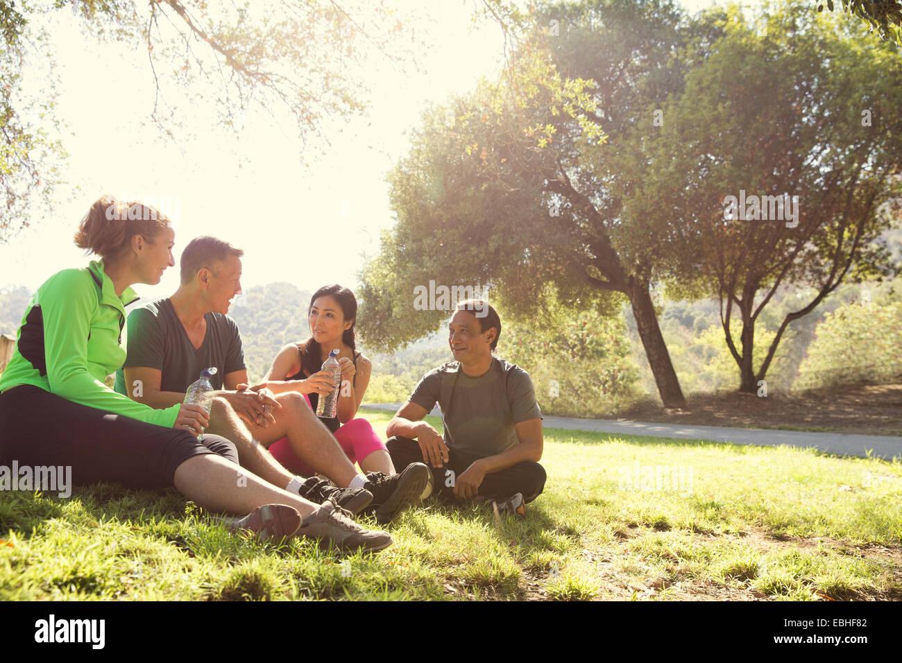 Vier Reifen männlichen und weiblichen Läufer sitzen im Chat im Park Stockbild
