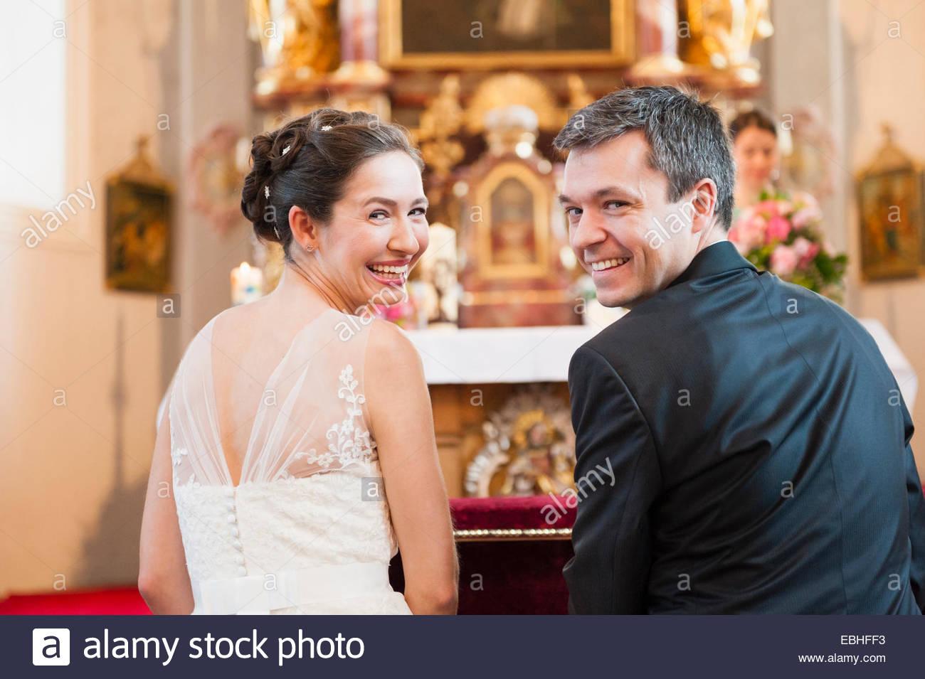 Rückansicht von Braut und Bräutigam am Altar der Kirche Stockbild