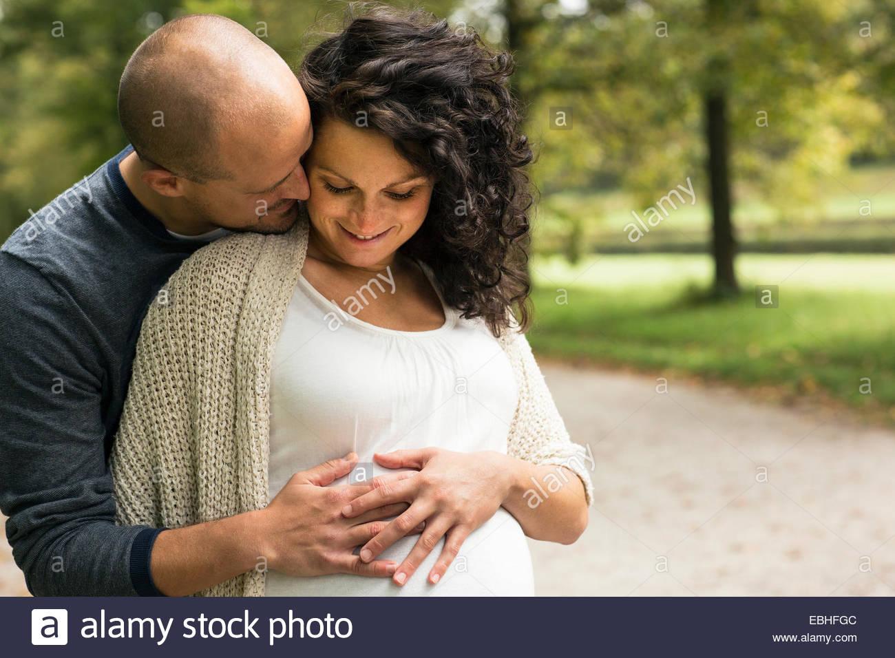 Schwangere paar streichelt Bauch im park Stockfoto