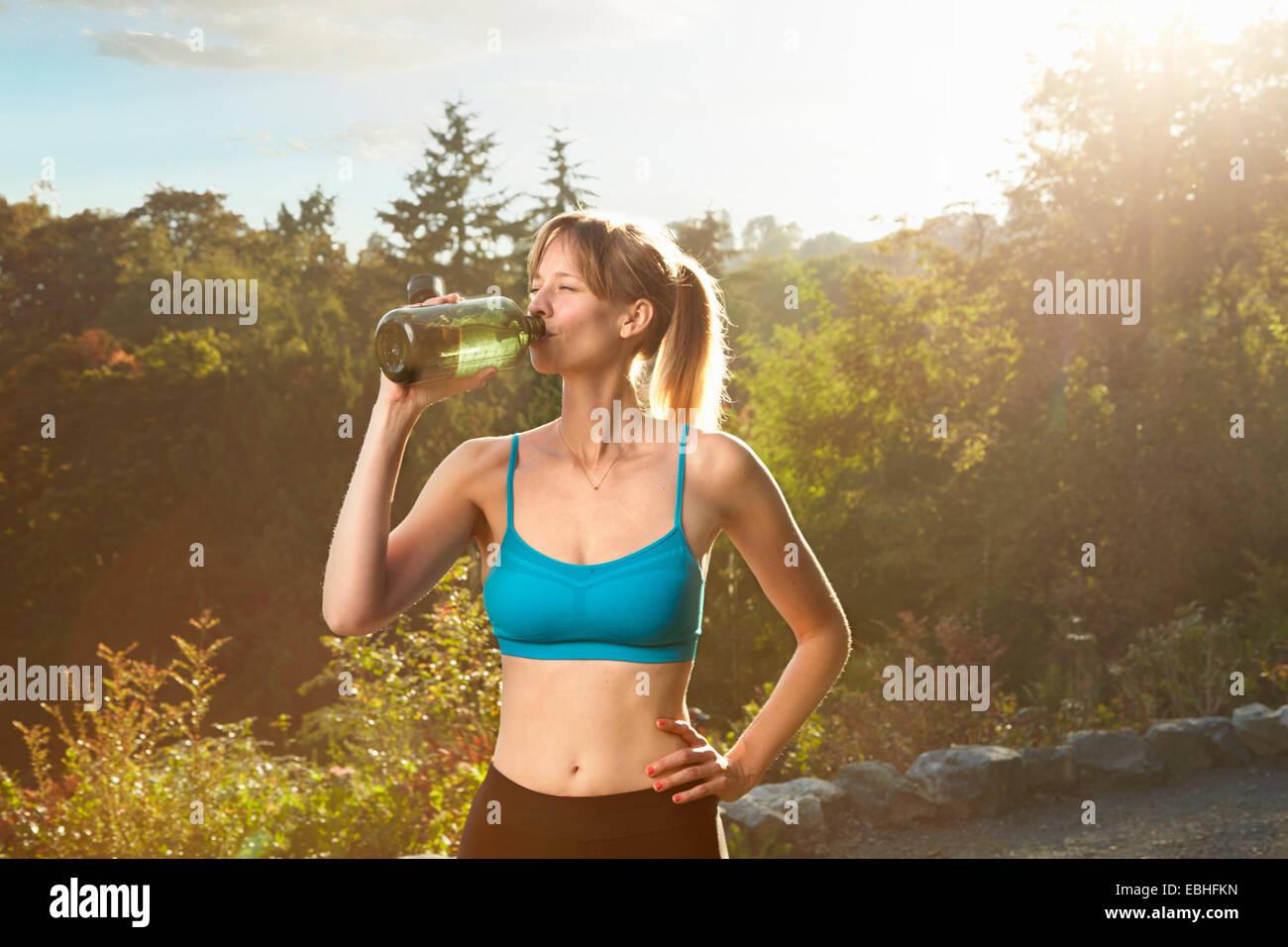 Mitte Erwachsene weibliche Läufer Wasser eine Pause im park Stockbild