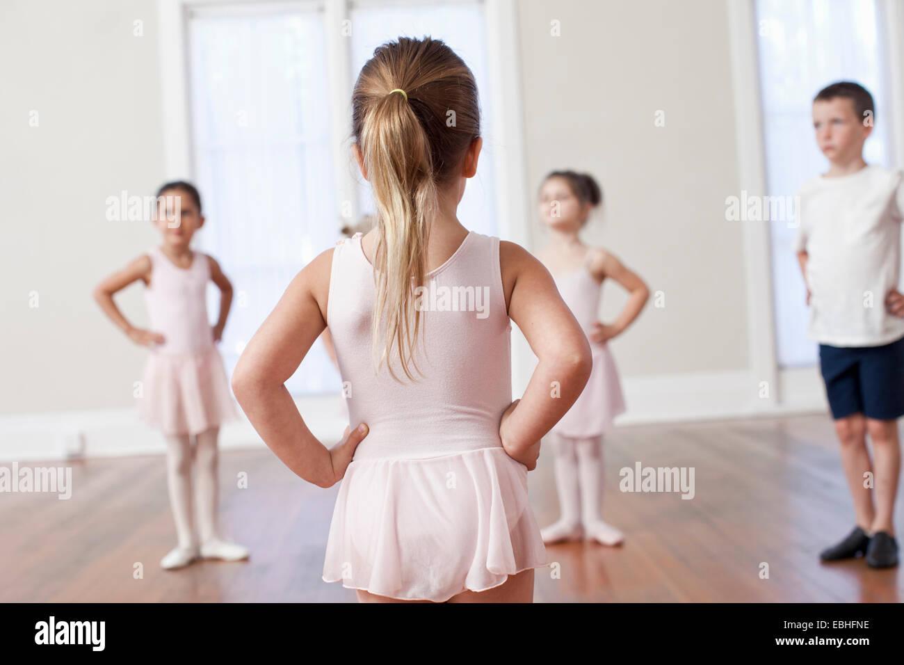 Vier Kinder üben Ballett mit Händen auf den Hüften in die Ballettschule Stockbild
