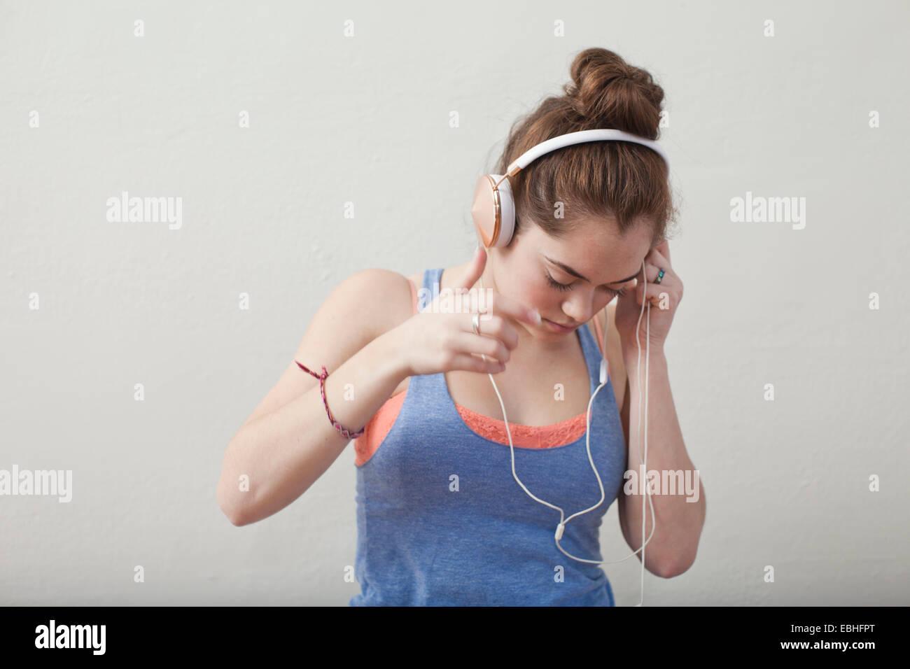 Teenager-Mädchen hören über Kopfhörer in der Ballettschule Stockbild