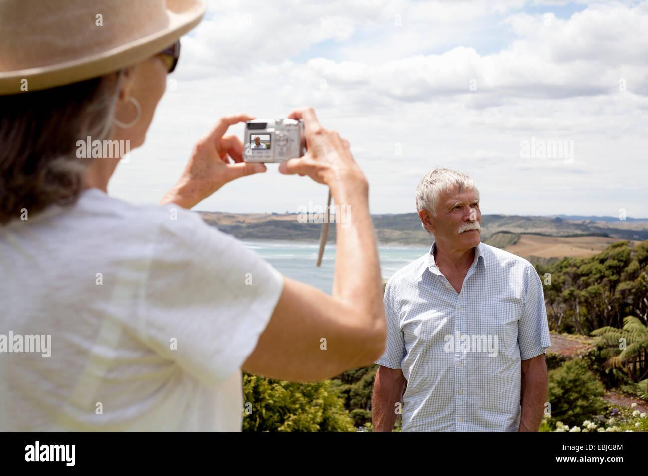 Frau fotografieren Mann, Ozean im Hintergrund, Raglan, Neuseeland Stockbild