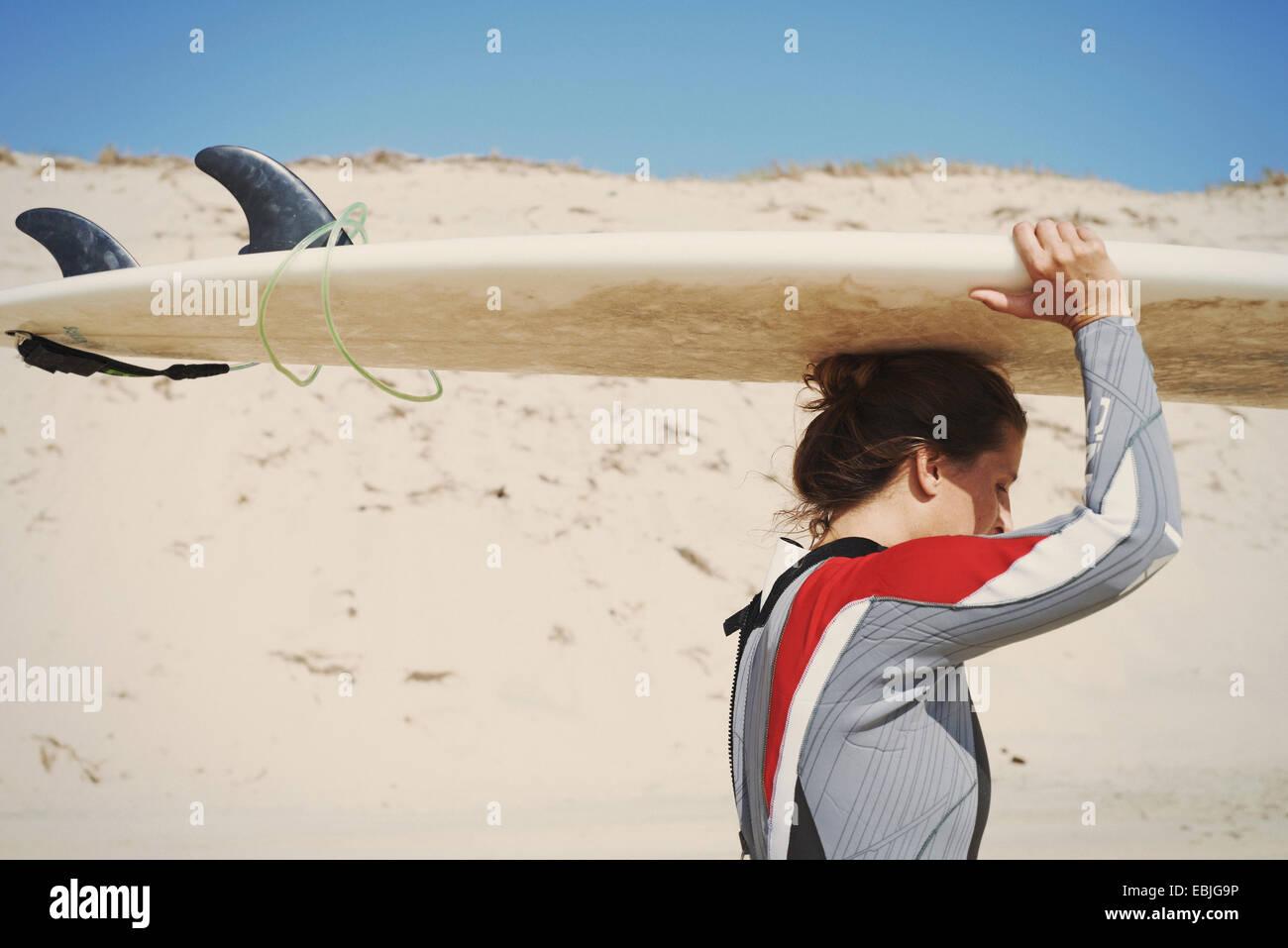 Surfer mit Surfbrett auf Kopf am Strand, Lacanau, Frankreich Stockbild