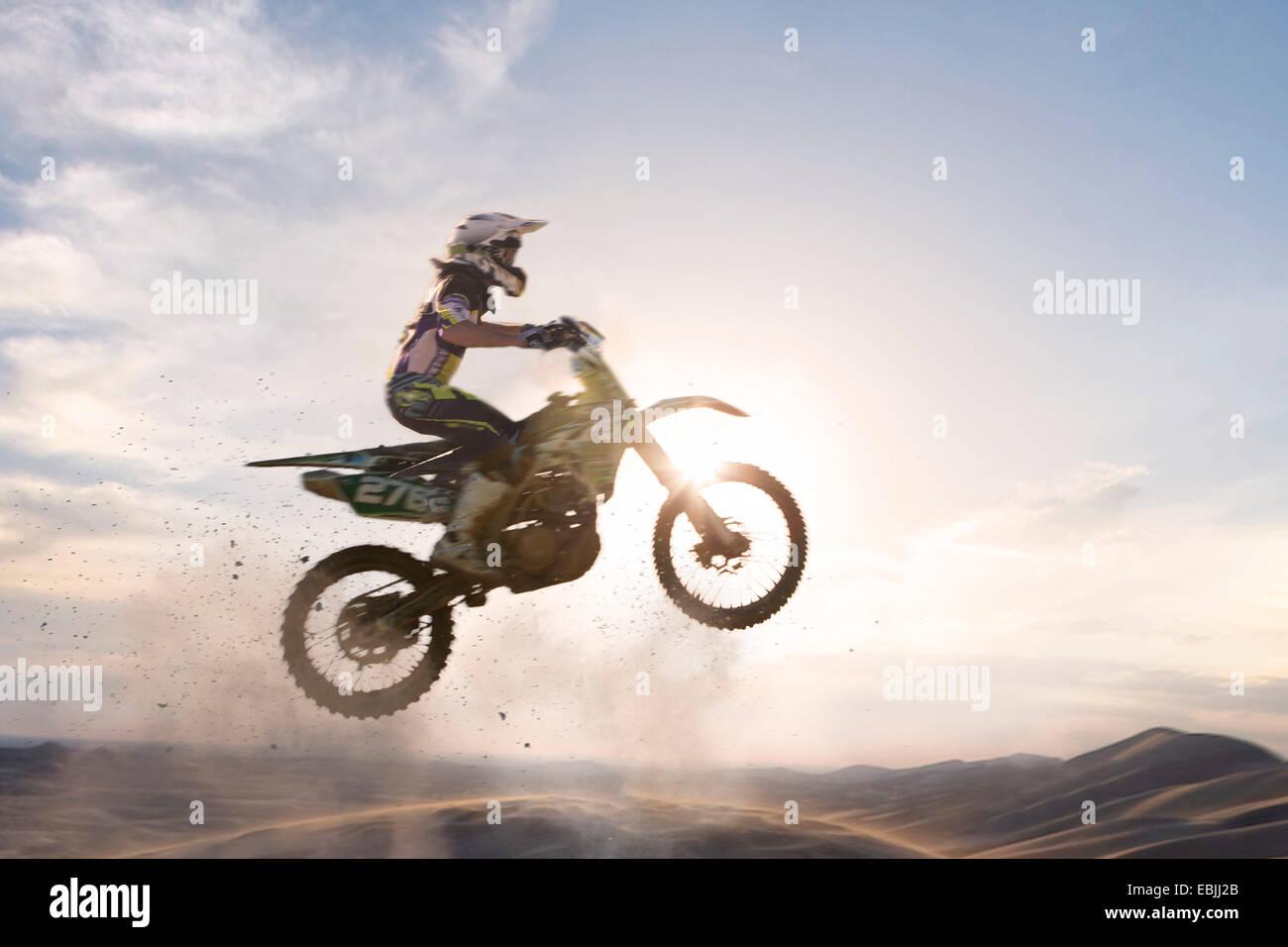Silhouette, jungen männlichen Motocross Racer über Schlamm Track springen Stockbild