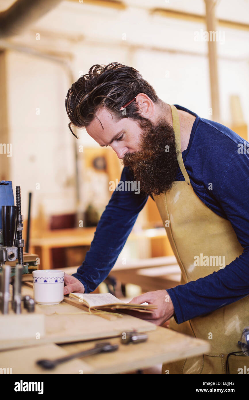 Mitte adult Handwerker Notizbuch in der Orgelwerkstatt überprüfen Stockbild