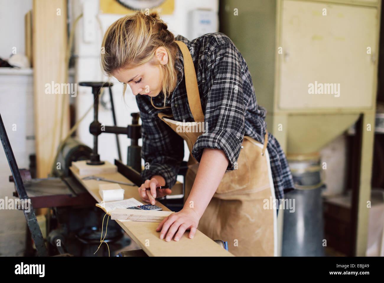 Junge Handwerkerin mit Taschenrechner in Orgel-Werkstatt Stockbild