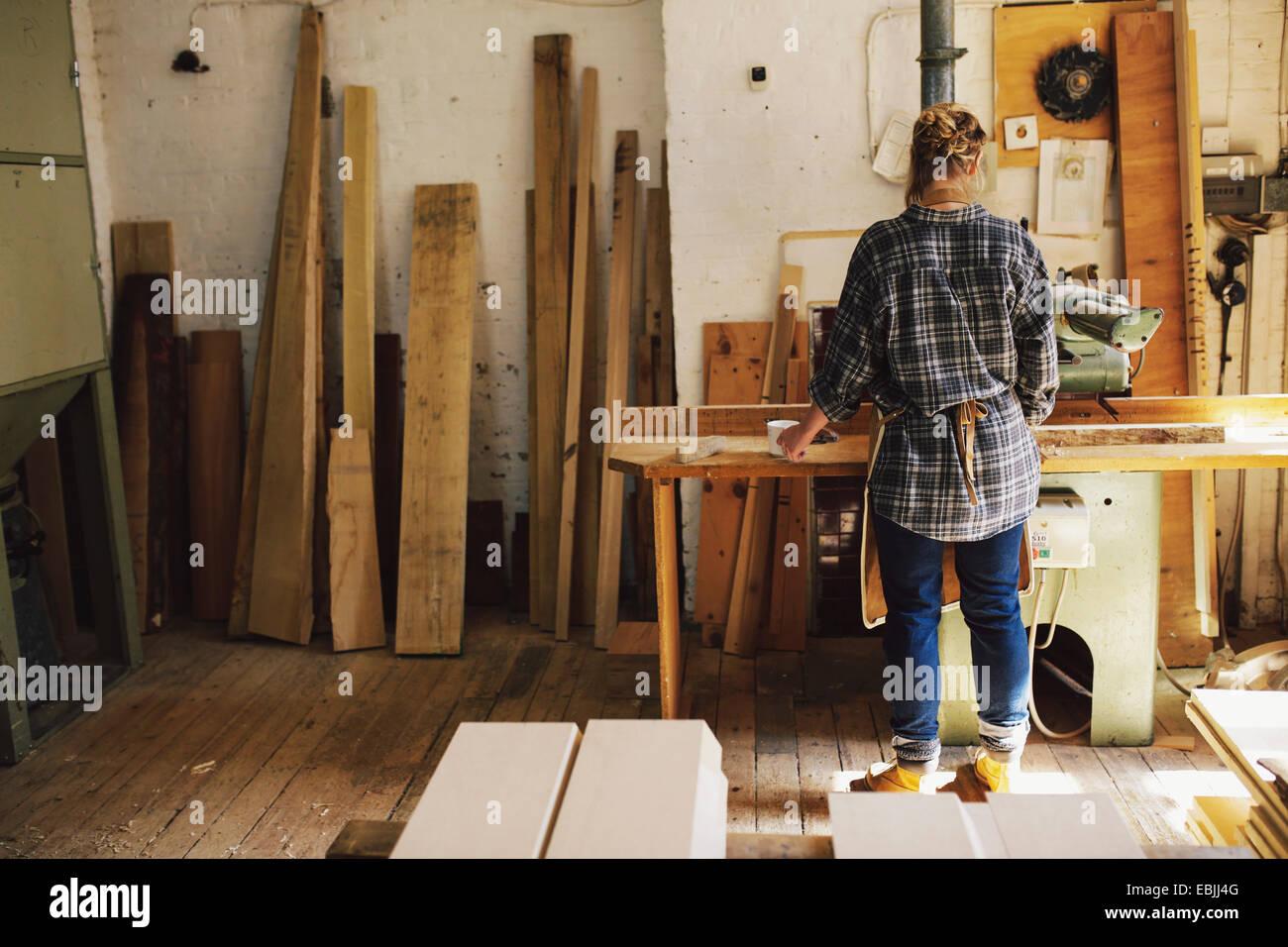 Junge Handwerkerin an Werkbank in Orgel-workshop Stockbild