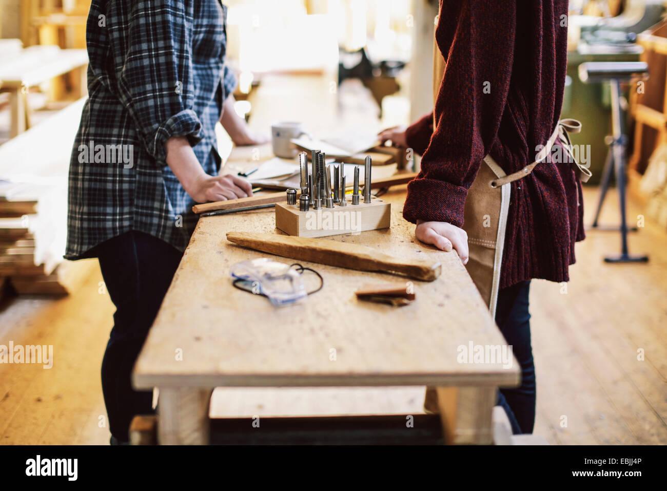 Blick auf zwei Handwerkerinnen an Werkbank in Rohr Orgelwerkstatt beschnitten Stockbild