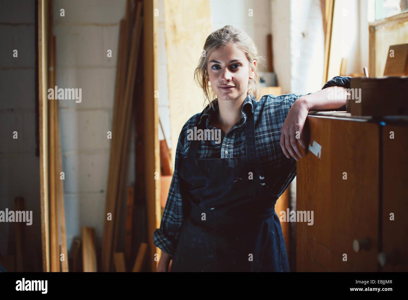 Porträt des jungen Handwerkerin stützte sich auf Schrank in Orgelwerkstatt Stockbild
