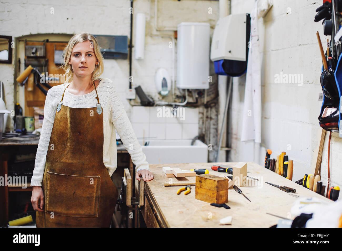 Porträt des jungen Handwerkerin stützte sich auf die Werkbank in Orgelwerkstatt Stockbild