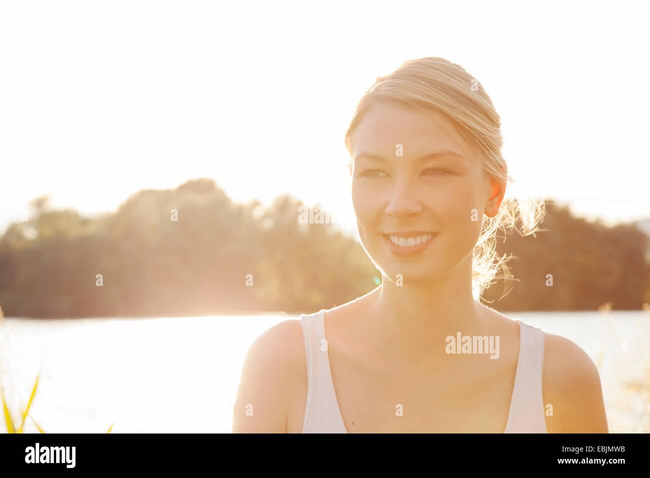 Hintergrundbeleuchtung Porträt der jungen Frau am Flussufer, Donauinsel, Wien, Österreich Stockbild