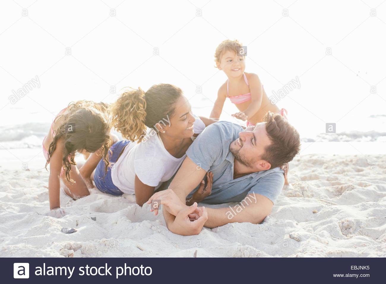 Ehepaar mit zwei Mädchen spielen kämpfen am Strand, Toskana, Italien Stockbild