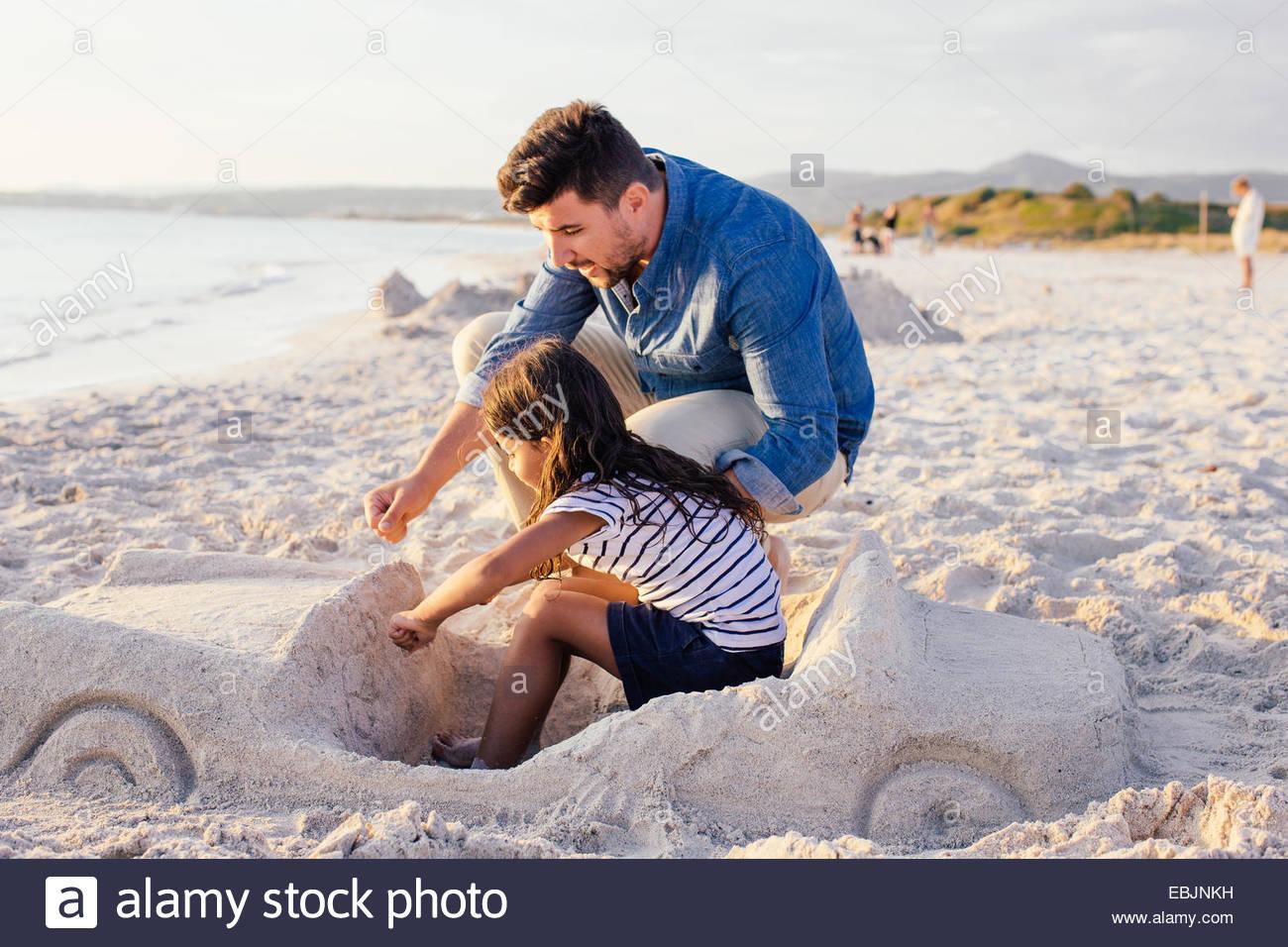 Mädchen und Vater mit anspruchsvollen Auto Sandburg am Strand, Toskana, Italien Stockbild